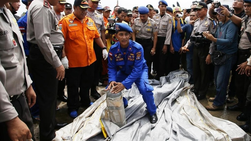 FILE - In this Thursday, Jan. 1, 2015 file photo, Indonesian police carry parts of a plane found floating on the water near the site where AirAsia Flight 8501 disappeared, at Kumai port in Pangkalan Bun, Thursday, Jan. 1, 2015. It took nearly two years to find the black boxes from Air France Flight 447, but the Rio de Janeiro to Paris flight that fell into the Atlantic Ocean in the early hours of June 1, 2009, could offer insight into what may have gone wrong on AirAsia's Flight 8501. (AP Photo/Achmad Ibrahim, File)