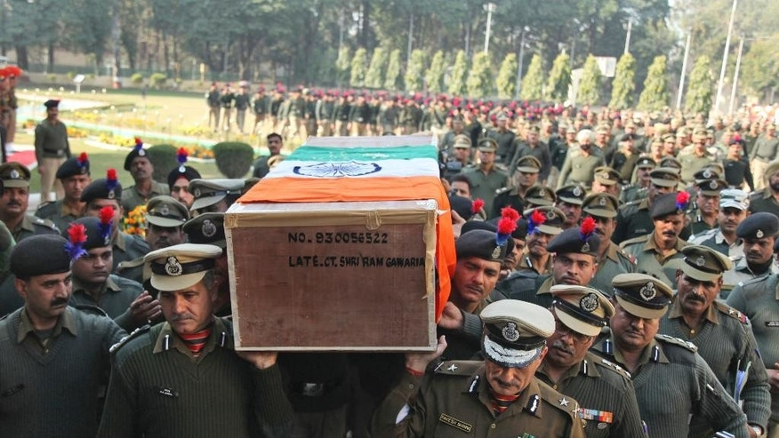 Indian Border Security Force (BSF) officers carry the coffin of their colleague who was killed in a India Pakistan cross border firing, in Jammu, India, Thursday, Jan. 1, 2015. Indian and Pakistani troops exchanged fire Wednesday near the cease-fire line that divides the disputed Himalayan region of Kashmir, leaving two dead on the Pakistani side and one on the Indian side, officials said. (AP Photo/Channi Anand)