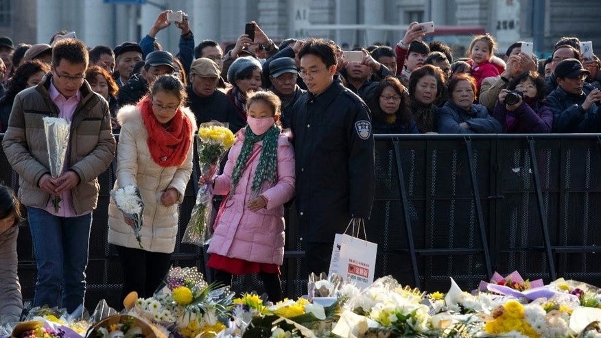 Residents lay flowers for victims of a deadly stampede in Shanghai, China, Friday, Jan. 2, 2015.  Authorities were still investigating the cause of the stampede late Wednesday night, but street vendors, residents, taxi drivers and other witnesses say the city failed to prepare for the massive turnout. (AP Photo/Ng Han Guan)