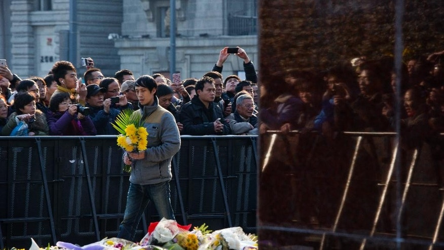 A man arrives to lay flowers for victims of a stampede in Shanghai, China, Friday, Jan. 2, 2015.  Authorities were still investigating the cause of the stampede late Wednesday night, but street vendors, residents, taxi drivers and other witnesses say the city failed to prepare for the massive turnout. (AP Photo/Ng Han Guan)