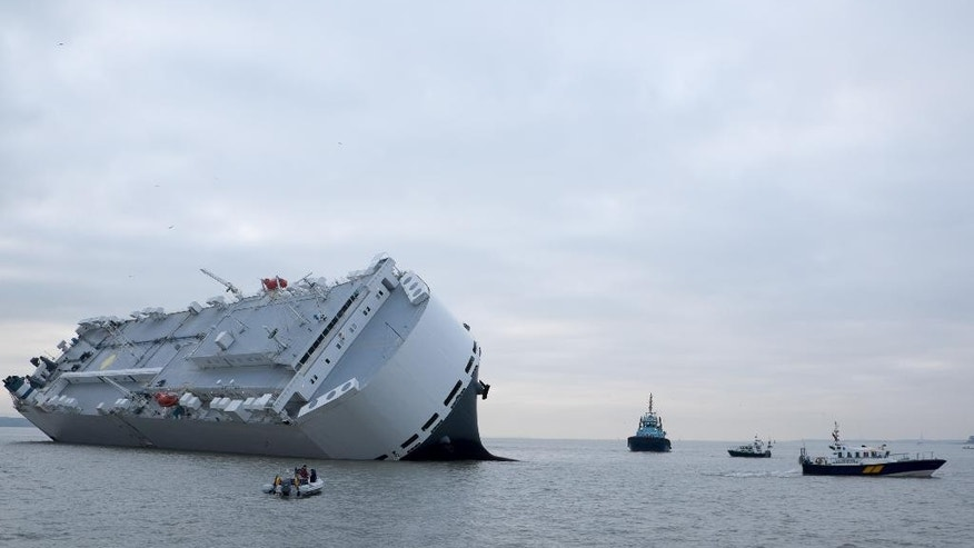 Small boats sail round the Hoegh Osaka car transporter cargo ship that ran aground in the Solent, off the Isle of Wight Sunday Jan. 4, 2015. The crew members of the Hoegh Osaka were taken to safety by a coastguard helicopter and lifeboats after it became stranded on Bramble Bank, in the Solent between Southampton and the Isle of Wight. (AP Photo/ Francis Bigg Photography)