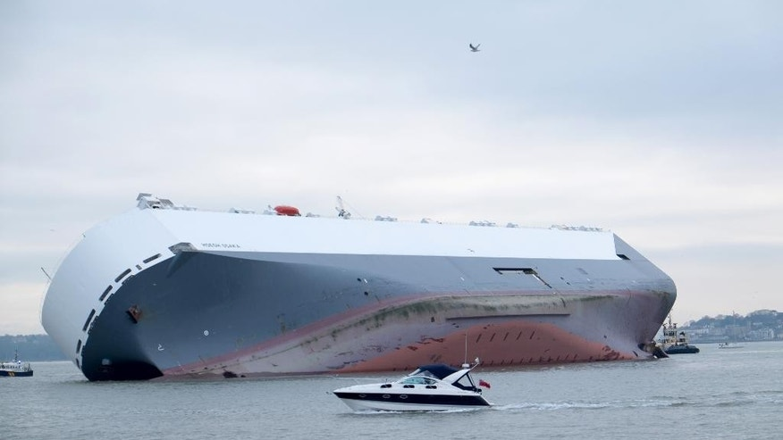 A small boat sails past the Hoegh Osaka car transporter cargo ship that ran aground in the Solent, off the Isle of Wight Sunday Jan. 4, 2015. The crew members of the Hoegh Osaka were taken to safety by a coastguard helicopter and lifeboats after it became stranded on Bramble Bank, in the Solent between Southampton and the Isle of Wight. (AP Photo/ Francis Bigg Photography)