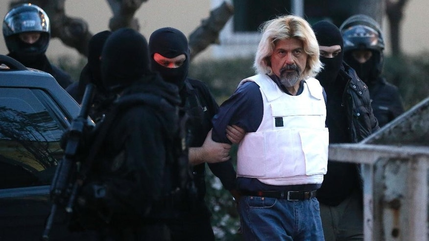 Jan. 4, 2015: One of Greece's most-wanted fugitives Christodoulos Xiros is escorted by anti-terror police officers to the prosecutor in Athens. (AP)