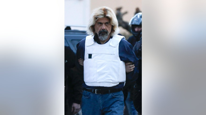 One of Greece's most-wanted fugitives Christodoulos Xiros is escorted by anti-terror police officers to the prosecutor in Athens on Sunday, Jan. 4, 2015. Xiros was captured Saturday, Jan. 3 nearly a year after he failed to return to prison while on a furlough. Xiros is serving six life terms, plus 25-years, for his role as a member of terrorist group 17 November.(AP Photo/Petros Giannakouris)