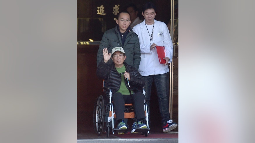 Former Taiwan President Chen Shui-bian waves to supporters as he is wheeled in a chair from the Taichung prison by his son Chen Chih-chung Monday, Jan. 5, 2015 in Taichung, Taiwan. Chen was granted a one-month medical parole Monday for treatment of neural degeneration, more than four years into his 20-year prison sentence for corruption. But he must return to prison to serve the remainder of his sentence if his condition improves. (AP Photo)