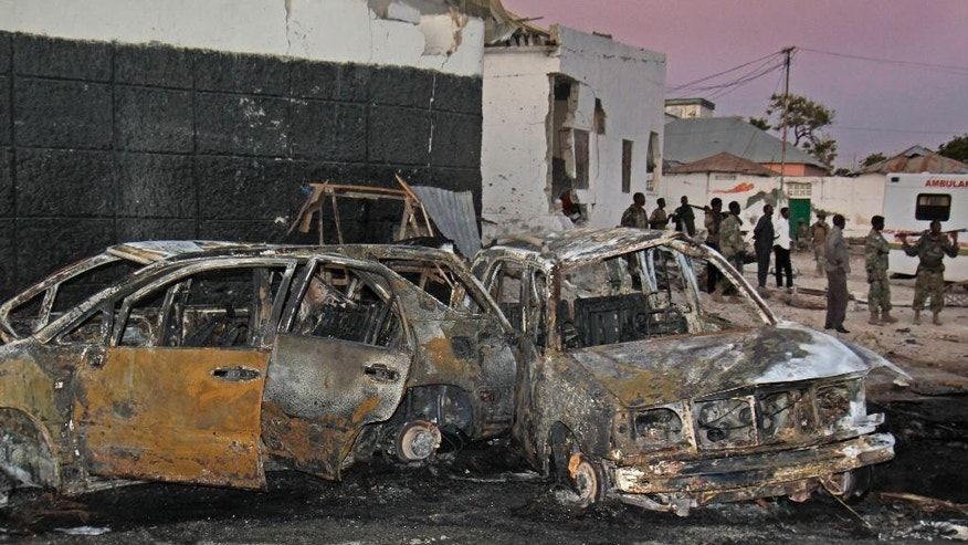 "Somali soldiers stand near the wreckage at the scene of a car bomb attack that targeted a moving convoy of Somalia's U.S.-trained elite forces, at dusk in Mogadishu, Somalia, Sunday, Jan. 4, 2015. The suicide car bomber blew himself up near the convoy of elite ""Alpha Group"" troops on the airport road in Mogadishu, killing at least four people, a Somali police officer said Sunday. (AP Photo/Farah Abdi Warsameh)"