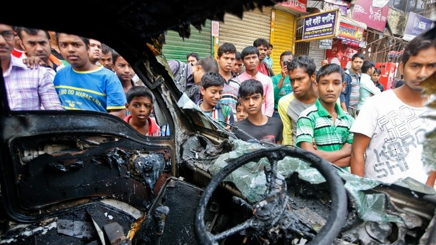 Bangladeshi people gather near a burnt vehicle, torched by Bangladesh Nationalist Party supporters and activists of Islami Chhatra Shibir, student wing of the Jamaat-e-Islami party,  in Dhaka, Bangladesh, Monday, Jan. 5, 2015. Two men on a motorbike opened fire on a group of anti-government activists in northwestern Bangladesh on Monday, killing two amid heightened tensions on the anniversary of a general election boycotted by a major opposition alliance last year, a local opposition leader said. (AP Photo/Suvra Kanti Das)