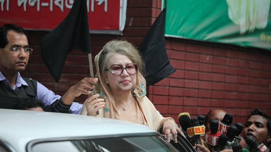 Bangladesh's former Prime Minister Khaleda Zia holds a black flag as she stands at her office in Dhaka, Bangladesh, Monday, Jan. 5, 2015. Two men on a motorbike opened fire on a group of anti-government activists in northwestern Bangladesh on Monday, killing two amid heightened tensions on the anniversary of a general election boycotted by a major opposition alliance last year, a local opposition leader said. (AP Photo/Suvra Kanti Das)