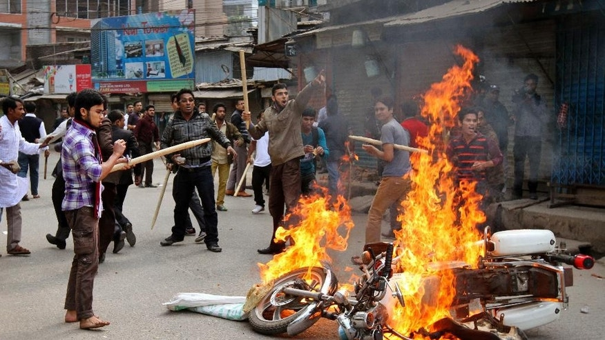 Bangladesh Nationalist Party and Jamaat-e-Islami party activists set fire to a police motorbike  in Dhaka, Bangladesh, Monday, Jan. 5, 2015. Two men on a motorbike opened fire on a group of anti-government activists in northwestern Bangladesh on Monday, killing two amid heightened tensions on the anniversary of a general election boycotted by a major opposition alliance last year, a local opposition leader said. (AP Photo/S.K. Hasan Ali)