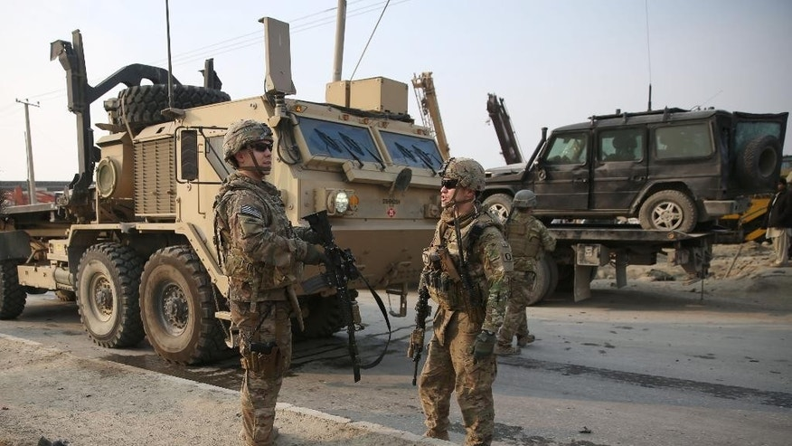 U.S. and British soldiers talk at the site of a suicide car bomb attack in Kabul, Afghanistan Monday, Jan. 5, 2015. The bomber struck near the headquarters of the European police training mission in Kabul, killing one Afghan civilian and wounding several others nearby. (AP Photo/Massoud Hossaini)