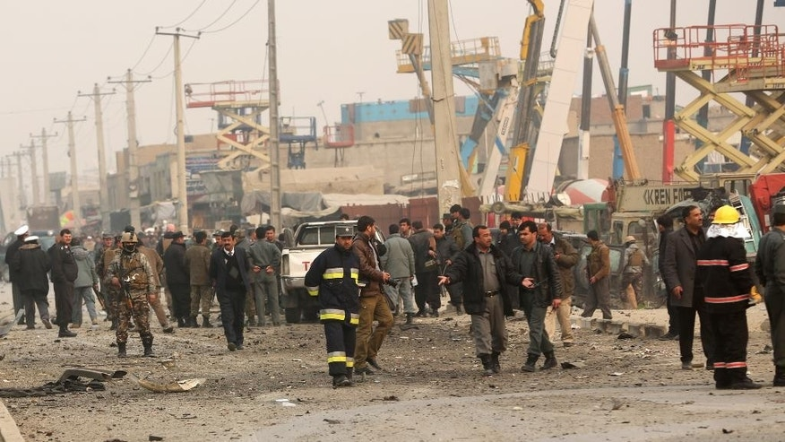 Afghan security forces inspect the site of a suicide attack in Kabul, Afghanistan Monday, Jan. 5, 2015. A suicide car bomber has struck near the headquarters of the European police training mission in Kabul, killing one Afghan civilian and wounding several others nearby. (AP Photo/Massoud Hossaini)