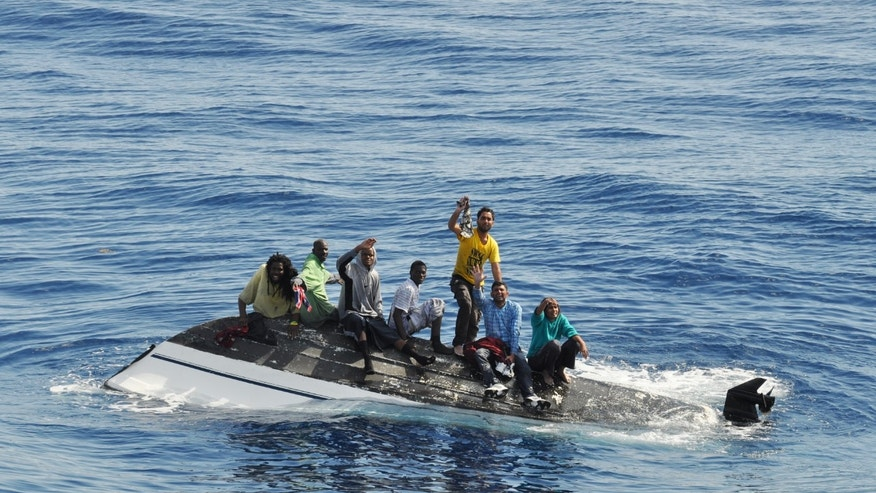 In this Feb. 6, 2014 photo made available by the USCG shows a group of migrants standing on their overturned boat off the coast of Port St. Lucie, Fla. The migrants were from Haiti, India and the Bahamas. The USCG retrieved three deceased women. According to the U.S. Coast Guard, the flow of migrants through the Caribbean Sea, the Atlantic Ocean and the Florida Straits in the fiscal year that ended Sept. 30 included 5,585 Haitians and 3,940 Cubans, along with hundreds of people from the Dominican Republic and other countries in the Caribbean and elsewhere. (AP Photo/United States Coast Guard)