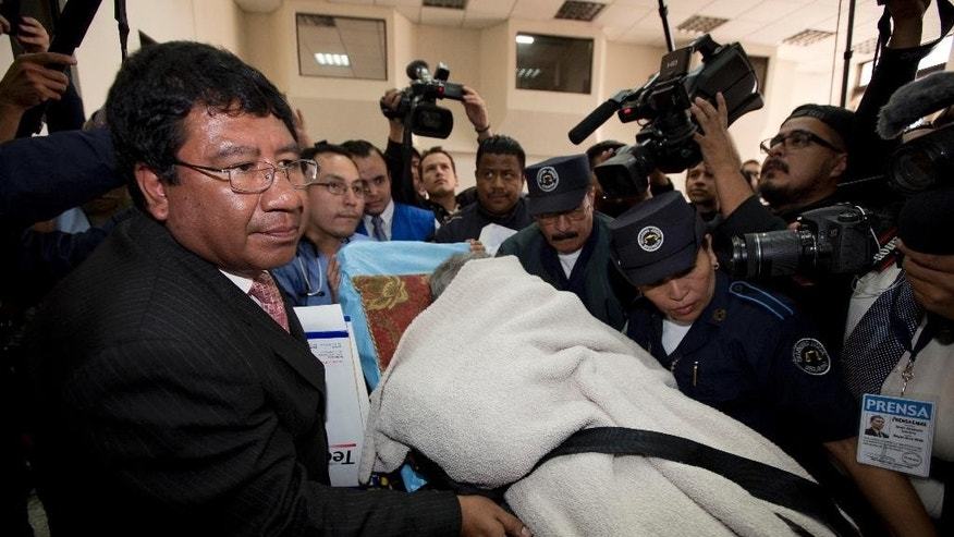 Former dictator Efrain Rios Montt enters the court room while he is carried on a stretcher and covered by a blanket in Guatemala City, Monday, Jan. 5, 2015. Rios Montt was forced to attend his trail for genocide after the court gave him an hour to present himself to the courtroom. His attorneys had alleged that he could not attend due to health reasons but the court rejected the appeal. (AP Photo/Moises Castillo)