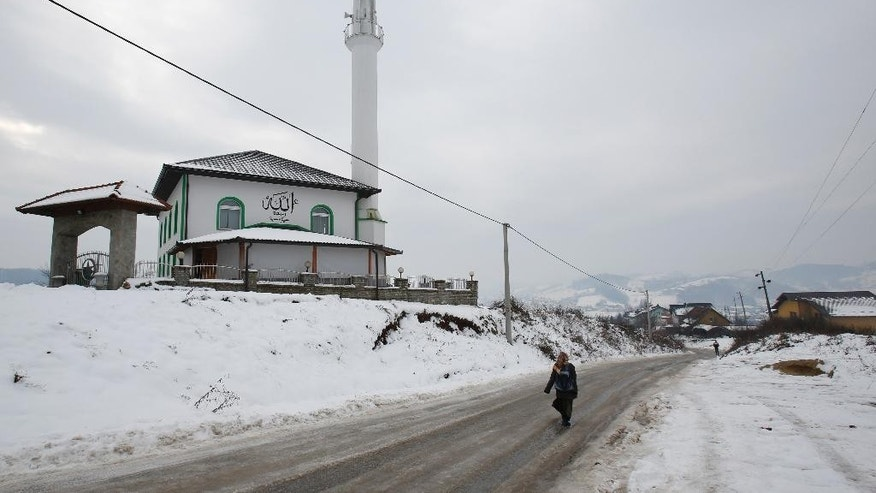 In this photo taken Saturday, Jan. 3, 2015, people make their way past the mosque where Bosnian imam Selvedin Beganovic was attacked in the village of Trnovi, near Velika Kladusa, 370 kilometers (230 miles) northwest of Sarajevo, Bosnia. For Beganovic, his compatriots have no business fighting in Syria no matter how many times Muslim extremists try to kill him for saying so. The imam has suffered seven assaults blamed on Muslim extremists in the past year - with three just in the past month. (AP Photo/Amel Emric)