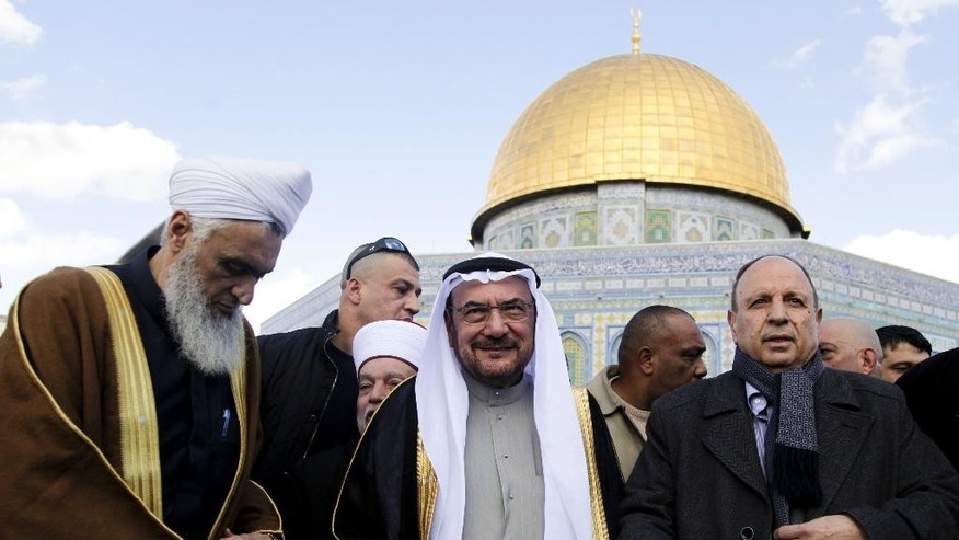 Iyad Madani, center, Secretary-General of the 57-nation Organization of Islamic Cooperation, stands in front of the Dome of the Rock shrine in Jerusalem Monday Jan. 5, 2015. Madani paid a rare visit to Jerusalem's Al-Aqsa Mosque, urging Muslims to follow suit and come to the city in a bid to strengthen Palestinian claims to the holy site. (AP Photo/Mahmoud Illean)