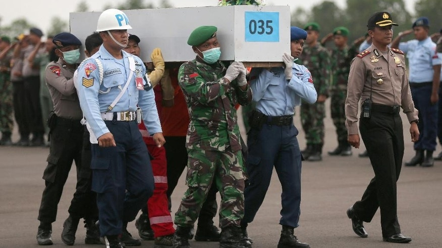Members of the National Search And Rescue Agency and Indonesian soldier carry a coffin of a victim who was aboard the AirAsia Flight 8501 at the airport in Pangkalan Bun, Monday, Jan. 5 2015.  Highlighting the depth of Indonesia's air safety problems, the transportation ministry announced harsh measures Monday against everyone who allowed AirAsia Flight 8501 to take off without proper permits — including the suspension of the airport's operator and officials in the control tower. The crackdown comes as searchers continue to fight bad weather while combing the Java Sea for bodies and wreckage of the Airbus A320 that crashed Dec. 28.  (AP Photo/Tatan Syuflana)
