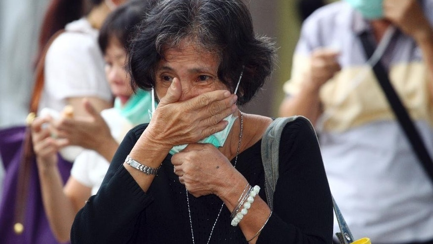 A relative of a victim of AirAsia Flight 8501 cries as she waits for the handover of the body to the family at a police hospital in Surabaya, East Java, Indonesia, Monday, Jan. 5, 2015. The Singapore-bound plane crashed into the sea 42 minutes after taking off on Dec. 28. (AP Photo/Firdia Lisnawati)