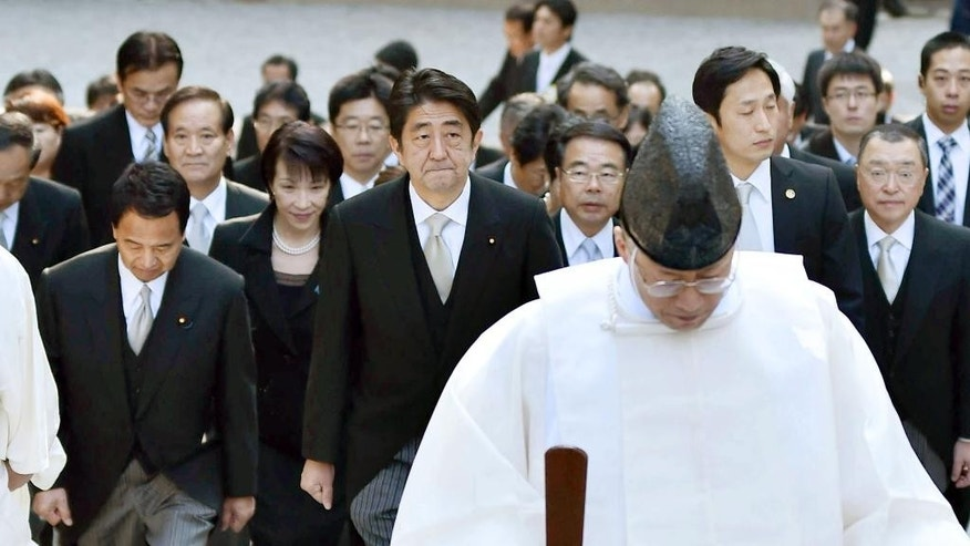 Japan's Prime Minister Shinzo Abe, center, and his cabinet ministers, escorted by a Shinto priest, arrive at the Grand Shrine of Ise, central Japan, for offering a new year's prayer Monday, Jan. 5, 2015.  Japanese Prime Minister Abe said Monday that his government would express remorse for World War II on the 70th anniversary of its end in August. (AP Photo/Kyodo News) JAPAN OUT, MANDATORY CREDIT