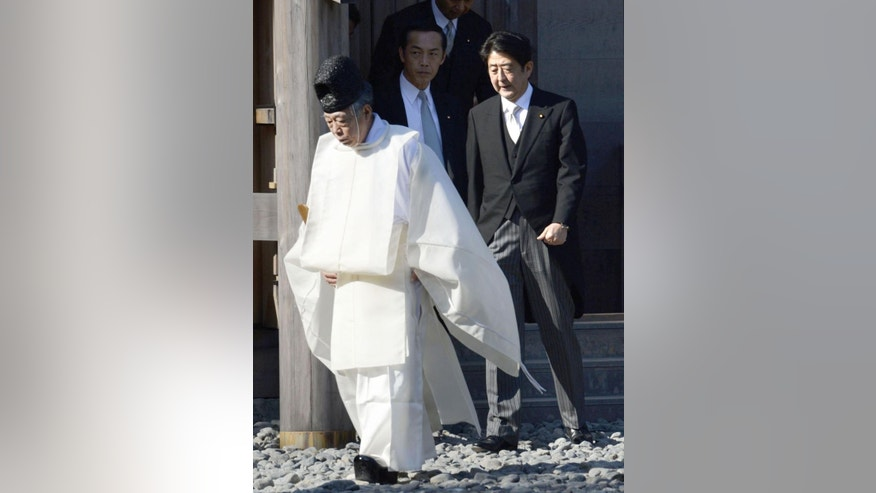 Japan's Prime Minister Shinzo Abe, right, is escorted by a Shinto priest, at the Grand Shrine of Ise, central Japan, Monday, Jan. 5, 2015.  Japanese Prime Minister Abe said Monday that his government would express remorse for World War II on the 70th anniversary of its end in August. (AP Photo/Kyodo News) JAPAN OUT, MANDATORY CREDIT