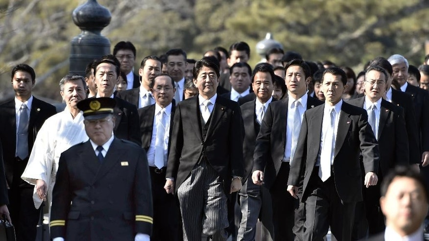 Japan's Prime Minister Shinzo Abe, center, surrounded by guards, arrives at the Grand Shrine of Ise, central Japan, for offering a new year's prayer Monday, Jan. 5, 2015.  Japanese Prime Minister Abe said Monday that his government would express remorse for World War II on the 70th anniversary of its end in August. (AP Photo/Kyodo News) JAPAN OUT, MANDATORY CREDIT
