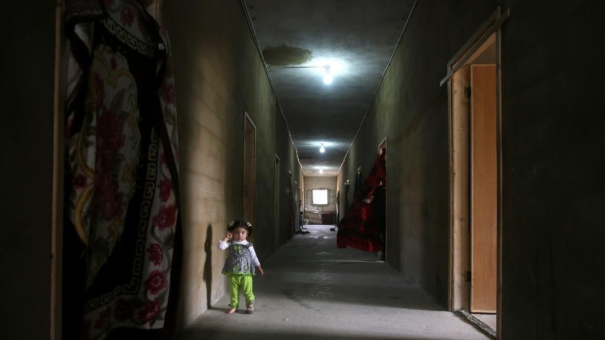 FILE - In this Thursday, May 29, 2014 file photo, a Syrian refugee girl stands in the corridor of a collective center where she lives with her family, in Kirbet Daoud village in Akkar, north Lebanon. Lebanon began limiting the flow of Syrians entering the country on Monday, Jan. 5, 2015, placing unprecedented restrictions on their entry, as it struggles to cope with a flood of asylum seekers fleeing the civil war next door. (AP Photo/Hussein Malla, File )