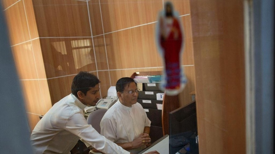 Newly appointed Cardinal Charles Maung Bo, right, works in his office room of archbishop house in Yangon, Myanmar, Monday, Jan. 5, 2015. Archbishop Bo was one of 20 new cardinals whose appointments were announced Sunday by Pope Francis. Bo's appointment comes as Myanmar grapples with major problems of religious intolerance, particularly by members of the Buddhist majority toward Muslims of the Rohingya ethnic minority. (AP Photo/Gemunu Amarasinghe)