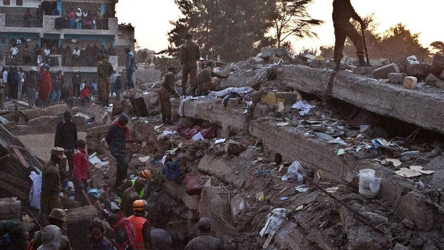 Rescue workers look for survivors at the site of the collapsed building in the capital Nairobi, Kenya , Monday, Jan. 5, 2015. The residential building in the Huruma neighborhood of Nairobi collapsed on Sunday and according to the Kenya Red Cross,  a dozen people have so far been rescued but an unknown number are still feared trapped. (AP Photo/Sayyid Azim)