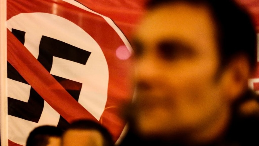 """Demonstrators stand in front of a banner with a  crossed-out swastika to protest against a planned rally of so-called 'Berlin Patriots against the Islamization of the West'  (BAERGIDA) in Berlin, Monday, Jan. 5, 2015.  Thousands of Germans were expected to demonstrate in four cities Monday night as opposition increases to weekly rallies in Dresden against the perceived """"Islamization of the West,"""" which have attracted growing numbers of supporters. Organizers of the demonstrations in Berlin, Stuttgart, Cologne and Dresden said they were rallying against racism and xenophobia to instead promote a message of tolerance.  (AP Photo/Markus Schreiber)"""