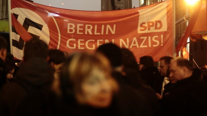 """Demonstrators stand in front of a banner of German Social Democratic party (SPD) with a  crossed-out swastika and the slogan 'Berlin against Nazis' to protest against a planned rally of  the so-called 'Berlin Patriots against the Islamization of the West' (BAERGIDA) in Berlin, Monday, Jan. 5, 2015. Thousands of Germans were expected to demonstrate in four cities Monday night as opposition increases to weekly rallies in Dresden against the perceived """"Islamization of the West,"""" which have attracted growing numbers of supporters. Organizers of thedemonstrations in Berlin, Stuttgart, Cologne and Dresden said they were rallying against racism and xenophobia to instead promote a message of tolerance.  (AP Photo/Markus Schreiber)"""