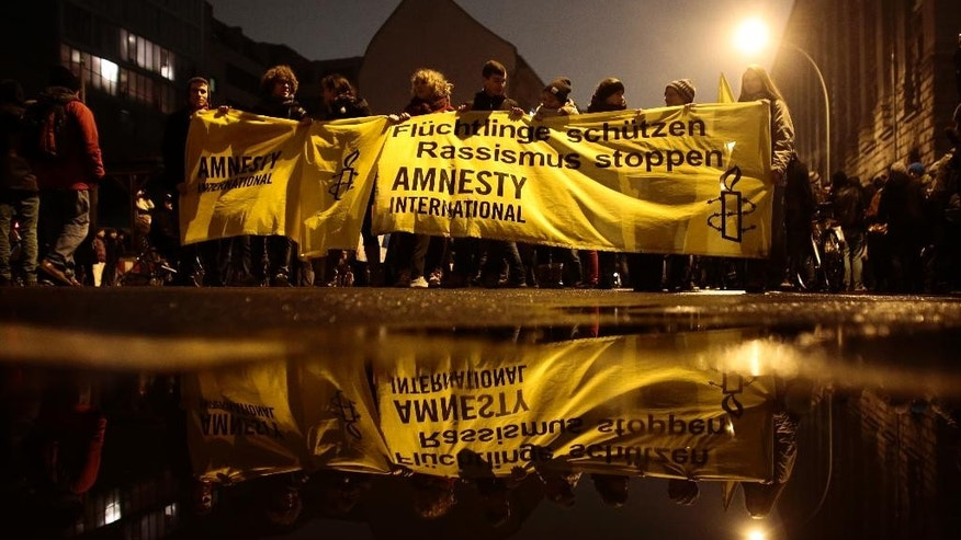 """Activists of Amnesty International with a banner  protest against a planned rally of so-called 'Berlin Patriots against the Islamization of the West' (BAERGIDA) in Berlin, Monday, Jan. 5, 2015. The banner reads: ' Shelter  Refugees, Stop Rassism'.  Thousands of Germans were expected to demonstrate in four cities Monday night as opposition increases to weekly rallies in Dresden against the perceived """"Islamization of the West,"""" which have attracted growing numbers of supporters. Organizers of thedemonstrations in Berlin, Stuttgart, Cologne and Dresden said they were rallying against racism and xenophobia to instead promote a message of tolerance. (AP Photo/Markus Schreiber)"""