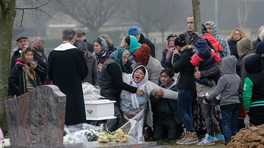 The mother of Maria Francesca, who died of sudden infant death syndrome, cries in front of the coffin of her baby during the funeral in Wissous, outside Paris, France, Monday, Jan. 5, 2015. Wissous offered a gravesite for the baby after the mayor of Champlan, where the child and mother lived, reportedly refused a burial plot. (AP Photo/Christophe Ena)