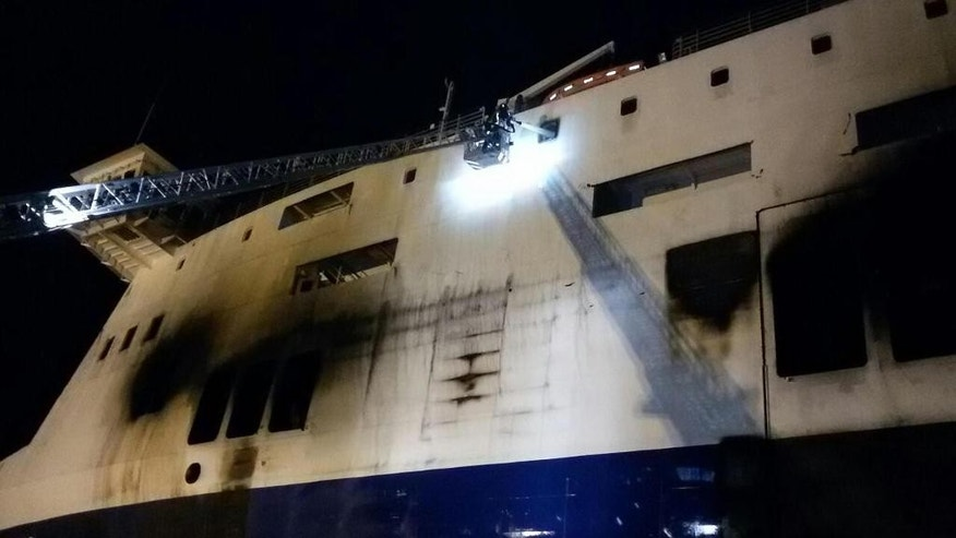Firefighters spray water in the charred Norman Atlantic Ferry in Brindisi's port on Sunday, Jan. 4, 2015. For a second day, fierce heat from a slow-burning blaze kept firefighters and other investigators on Saturday from searching the hold and vehicle decks of a Greek ferry for more bodies. At least 11 people perished in the pre-dawn blaze on Dec. 28 aboard the Norman Atlantic, on a voyage between Greece and Italy. Authorities fear more bodies might be inside the vehicle deck where the fire began. (AP Photo/Roberta Grassi)