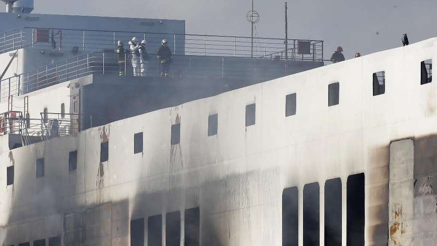 Firefighters and investigators work on the Norman Atlantic ferry after it was towed into the port of Brindisi, southern Italy, Saturday, Jan. 3, 2015. Wearing gas masks against the smoke, Italian firefighters and investigators boarded the charred Norman Atlantic ferry on Friday and retrieved a data recorder they hope will help them discover what caused a deadly blaze. Some parts of the ferry are still burning making difficult the search for any more bodies in the maritime disaster that has already killed 11 people.  (AP Photo/Antonio Calanni)