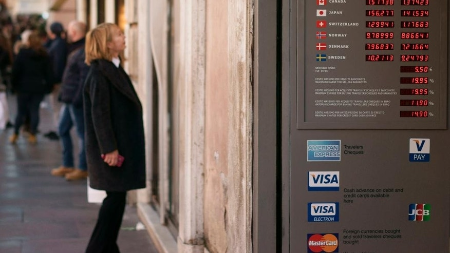 The billboard of  a currency office shows the exchange rates in Rome, Monday, Jan. 5, 2015. The euro sank to a nine-year low Monday as new doubts surfaced about Greece's commitment to the common currency bloc. European stocks mostly rose while Asian markets were mixed. (AP Photo/Andrew Medichini)