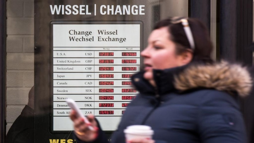 A woman walks past an exchange rate board at an exchange office in the center of Brussels on Monday, Jan. 5, 2015. The euro sank to a nine-year low Monday as new doubts surfaced about Greece's commitment to the common currency bloc. European stocks mostly rose while Asian markets were mixed. (AP Photo/Geert Vanden Wijngaert)
