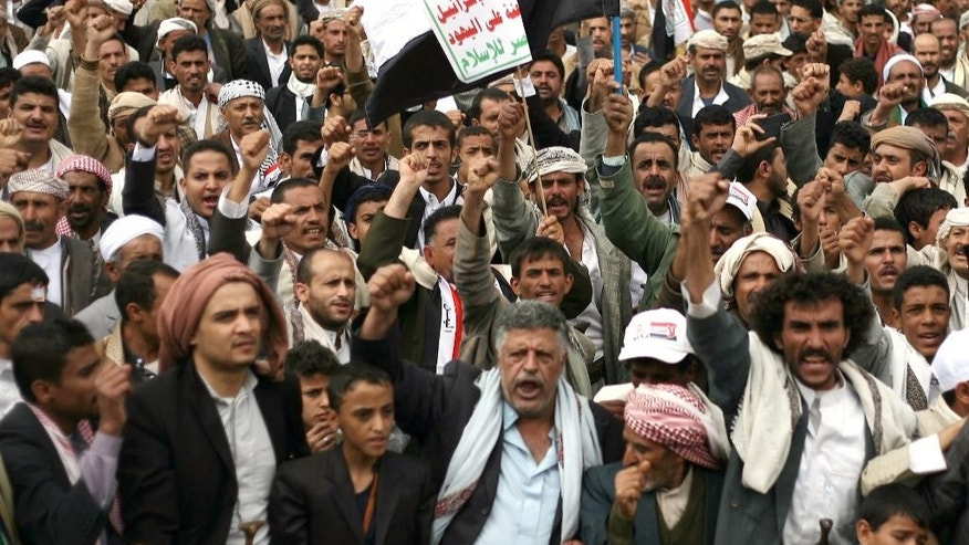 "FILE - In this Thursday, Oct. 9, 2014 file photo, Houthi Shiite rebels chant slogans during a protest near the site of a suicide bombing in Sanaa, Yemen. Arabic on a banner at center reads,""God is great. Death to America. Death to Israel. A curse on the Jews. Victory to Islam."" The turmoil in Yemen has taken on a sharply sectarian tone, pitting Sunnis against Shiites, to the benefit of Sunni al-Qaida.  (AP Photo/Abdullrhman Huwais, Fole)"