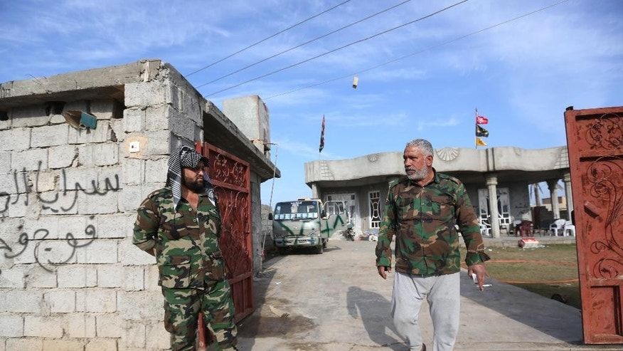 In this Saturday, Jan. 3, 2015 photo, Adnan Hassan, 59, right, and another Shiite militia member are seen outside a house they took over in Al-Rawashid a Sunni village outside the Iraqi city of Balad. 75 kilometers (45 miles) north of Baghdad, Iraq. He and his men last week helped Iraqi forces wrest the town from the hands of the Islamic State group. (AP Photo/Hadi Mizban)