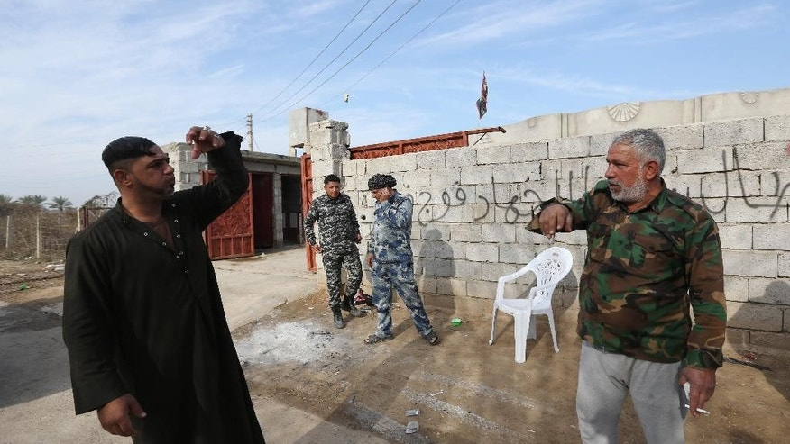 In this Saturday, Jan. 3, 2015 photo, Adnan Hassan, 59, right, and other Shiite militiamen are seen at a house they took over in Al-Rawashid a Sunni village outside the city of Balad. 75 kilometers (45 miles) north of Baghdad, Iraq. He and his men last week helped Iraqi forces wrest the area from the hands of the Islamic State group.(AP Photo/Hadi Mizban)