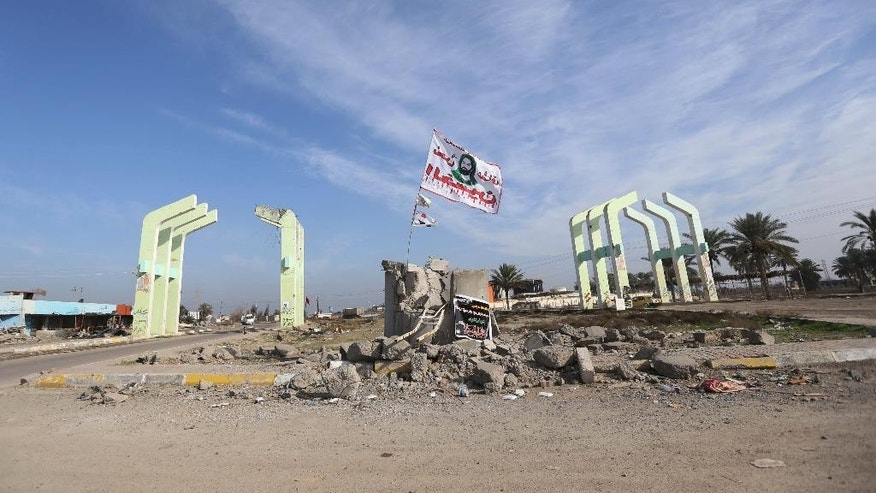 In this Saturday, Jan. 3, 2015 photo, a Shiite flag waves over a destroyed checkpoint at the entrance of Balad. 75 kilometers (45 miles) north of Baghdad, Iraq, after Shiite militias helped government forces push back Islamic State militants last week. (AP Photo/Hadi Mizban)
