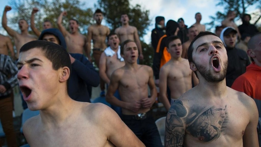 "In this photo taken on Saturday, Oct.  25, 2014, soccer fans of the team of ""Druzhba"" (Friendship) from Petrovka village support their team during a match at ""Yunost"" (Youth) stadium in Krasnogvardeiskoye, about 68 km., 42 miles north of Simferopol, Crimea. Crimea's soccer fans, especially the tough and boisterous young men who frequent games, are as devoted as ever, even as political tensions cloud the region's teams.  In the wake of Russia's annexation of the Black Sea peninsula from Ukraine, the European soccer federation UEFA in December banned Crimean soccer clubs from playing in Russian leagues.  Ukraine says Russia effectively stole three teams. (AP Photo/Alexander Zemlianichenko)"