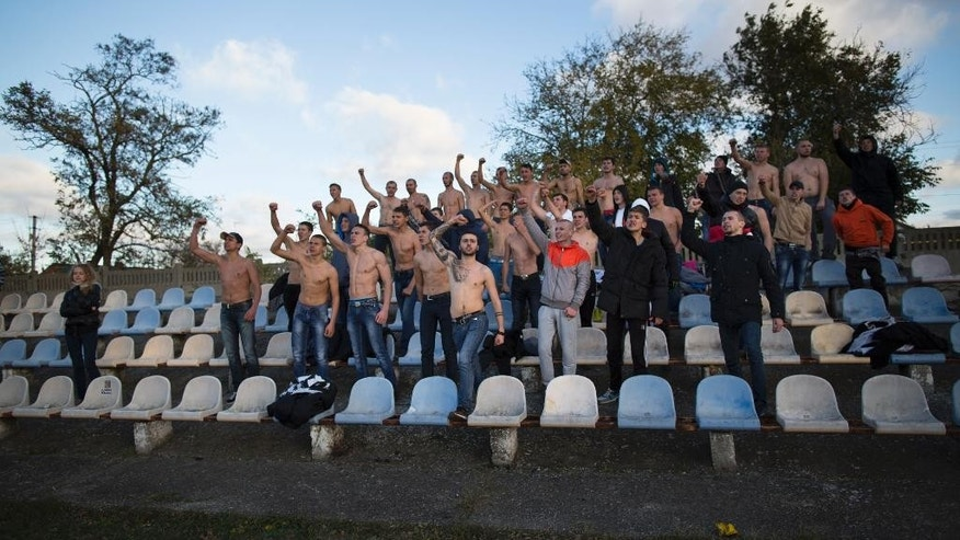 "In this photo taken on Saturday, Oct.  25, 2014, soccer fans of the team of ""Druzhba"" (Friendship) from Petrovka village support their team during a match at ""Yunost"" (Youth) stadium in Krasnogvardeiskoye, about 68 km. , 42 miles north of Simferopol, Crimea. Crimea's soccer fans, especially the tough and boisterous young men who frequent games, are as devoted as ever, even as political tensions cloud the region's teams.  In the wake of Russia's annexation of the Black Sea peninsula from Ukraine, the European soccer federation UEFA in December banned Crimean soccer clubs from playing in Russian leagues.  Ukraine says Russia effectively stole three teams. (AP Photo/Alexander Zemlianichenko)"