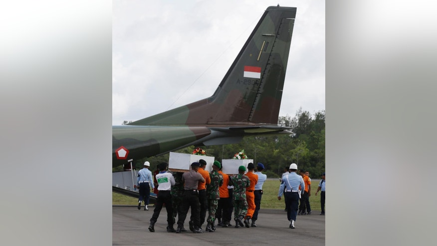 Members of the National Search and Rescue Agency carry coffins containing bodies of the victims aboard AirAsia Flight 8501 to transfer to Surabaya, at the airport in Pangkalan Bun, Indonesia Wednesday, Jan. 7, 2015. At least two divers plunged into the choppy waters early Wednesday during a break in the bad weather to search for two large objects suspected of being chunks of the fuselage of the AirAsia plane that crashed more than one week ago, an Indonesian official said. (AP Photo/Achmad Ibrahim)