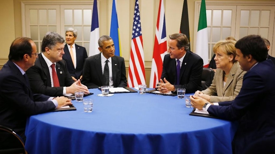 In this Thursday, Sept. 4, 2014 file photo U.S. President Barack Obama, fourth from left, is seated at a table with, from left to right: France's President Francois Hollande, Ukraine President Petro Poroshenko, British Prime Minister David Cameron, German Chancellor Angela Merkel and Italian Prime Minister Matteo Renzi during a NATO summit at Celtic Manor in Newport, Wales. Leaving combat operations in Afghanistan behind, NATO is shifting its focus to Europe in 2015 and the creation of its new ultra-rapid reaction force, designed as a deterrent to Russia. (AP Photo/Charles Dharapak, File)