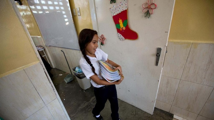 In this Dec. 11, 2014 photo, a public school student helps her teacher return government provided textbooks to the library after class in Caracas, Venezuela. Bolivarian textbooks introduced in 2011 include history traditionally left out of grade school education, and tie lessons to real-life examples in Venezuela. (AP Photo/Fernando Llano)