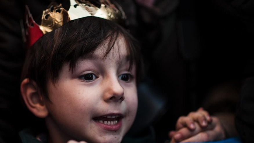EDS NOTE : SPANISH LAW REQUIRES THAT THE FACES OF MINORS ARE MASKED IN PUBLICATIONS WITHIN SPAIN. A boy wearing a crown watches the Cabalgata Los Reyes Magos (Cavalcade of the three kings) the day before Epiphany, in Pamplona, northern Spain, Monday, Jan. 5, 2015. It is a parade symbolizing the coming of the Magi to Bethlehem following the birth of Jesus. In Spain and many Latin American countries Epiphany is the day when gifts are exchanged. (AP Photo/Alvaro Barrientos)