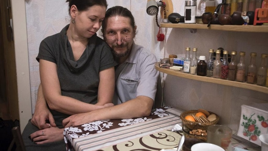 In this photo taken on Saturday, Dec.  27, 2014, Dmitry Dervenyov, 50, right, and his wife Svetlana Suvorova, 32, sit in their flat in St.Petersburg, Russia. Dmitry his wife Svetlana have finally managed to refinance their 15-year dollar mortgage loan with DeltaCredit bank into rubles on Friday, Dec. 23, 2014. The refinancing increased their monthly payments in rubles almost twice compared to the beginning of the year but it still made them feel safer.(AP Photo/Dmitry Lovetsky)