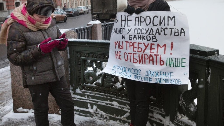 "In this photo taken on Sunday, Dec.  28, 2014, Oksana Li, right, stands with her son Gleb, 12,  in a one-person picket, holding a poster reading ""We are not asking for money from the state and banks, we demand not to take ours! "" in St.Petersburg, Russia. Oksana went to a one-person picket to protest the onerous foreign currency mortgage that threatens to ultimately deprive thousands of the country's mortgage borrowers of their apartments amid Russia's economic crisis. (AP Photo/Dmitry Lovetsky)"