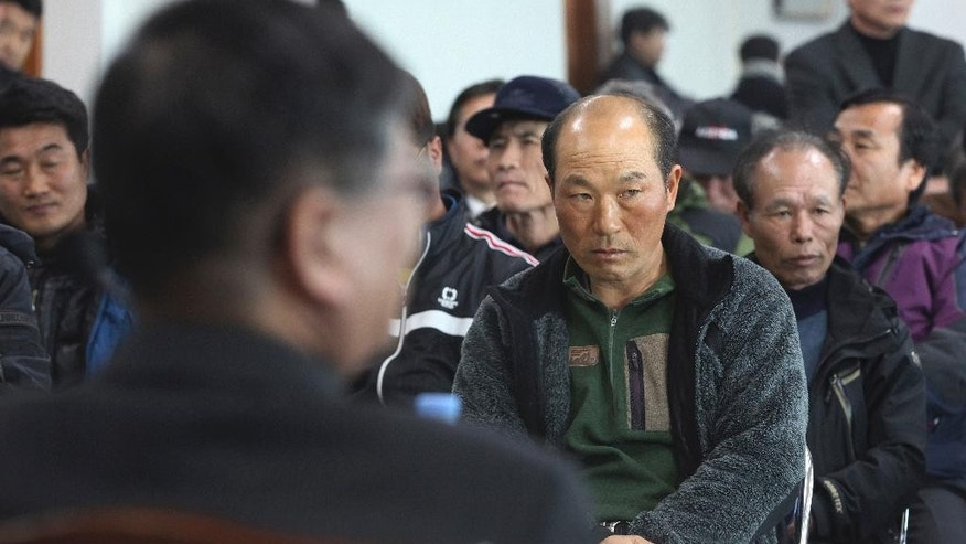 In this Feb. 19, 2014 photo, a government official, foreground, meets with salt farm owners and workers as a part of human rights inspection on Sinui Island, South Korea. Life as a salt-farm slave was so bad Kim Jong-seok sometimes fantasized about killing the owner who beat him daily. Freedom, he says, has been worse. In the year since police emancipated the severely mentally disabled man from the farm where he had worked for eight years, Kim has lived in a grim homeless shelter, preyed upon and robbed by other residents. He has no friends, no job training prospects or counseling, and feels confined and deeply bored. (AP Photo/Ahn Young-joon)