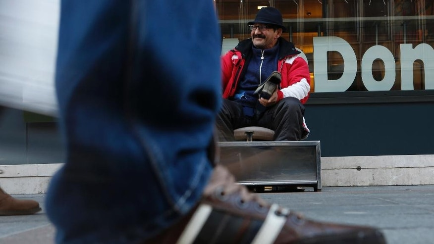 In this Friday, Dec. 19, 2014, photo shoe shiner Ramiz Hasani waits for customers on the main street in Sarajevo, Bosnia.  Ramiz inherited the business from his father, the beloved Uncle Misho, a Sarajevo legend who died beginning of this year after shining people's shoes for over 60 years. At the spot he sat and served his customers, Sarajevans put up a plaque to commemorate Uncle Misho and the mayor referred to him as a 'city symbol'. Ramiz says his father is the only Gypsy he heard of whom a city declared 'honorary citizen', gave him a pension and a small apartment as a gift just for his charm that was putting a smile on people's faces even during the 1992-95 war. (AP Photo/Amel Emric)