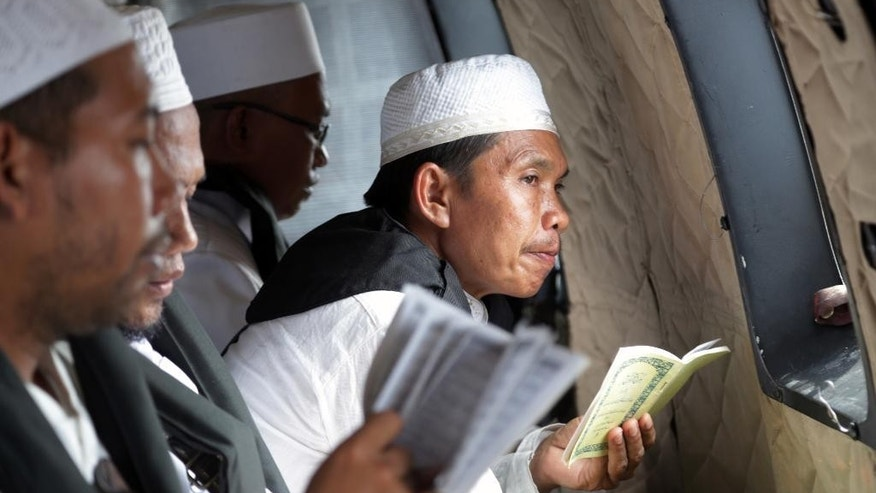 A Muslim cleric pauses as he reads a book of Quran verses during a prayer for the victims of AirAsia Flight 8501 inside an Indonesian Air Force NAS 332 Super Puma helicopter flying over the Java Sea off Pangkalan Bun, Central Borneo, Indonesia where the ill-fated jetliner went down, on Tuesday, Jan. 6, 2015. The Singapore-bound plane crashed into the sea 42 minutes after taking off on Dec. 28.  (AP Photo/Achmad Ibrahim, Pool)